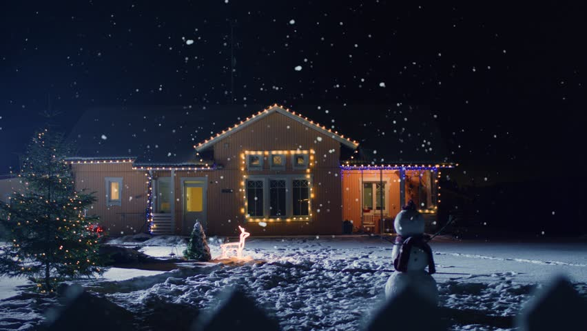 Idyllic House Decorated with Lights and Garlands for Christmas Eve. Front Yard Has Christmas Tree and Snowman. Soft Snow Falling Peacefully at Night. Shot on RED EPIC-W 8K Helium Cinema Camera.