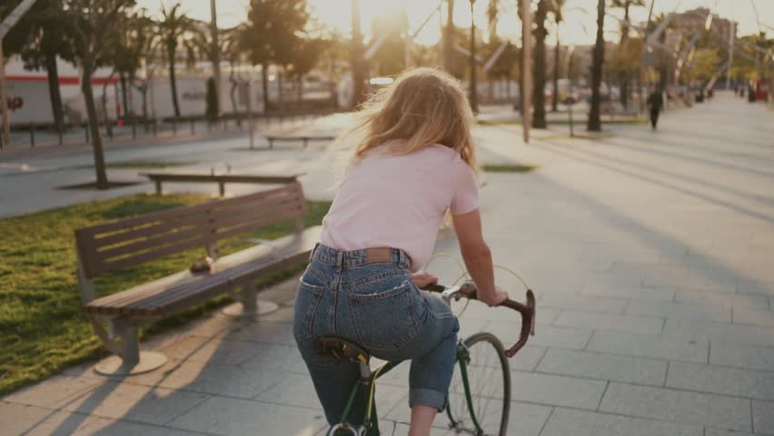 Slow motion of beautiful pretty young girl, woman with blonde hair look back at camera with happy, dreamy and romantic eyes, she rides bicycle on sunset filled park, concept forever young, summer
