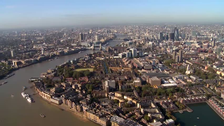 A wide travelling aerial shot of London skyline and the city. The camera follows a bend in the River Thames and we get a birds eye view of all the surrounding areas of London. HD shot from helicopter. | Shutterstock HD Video #1010298134