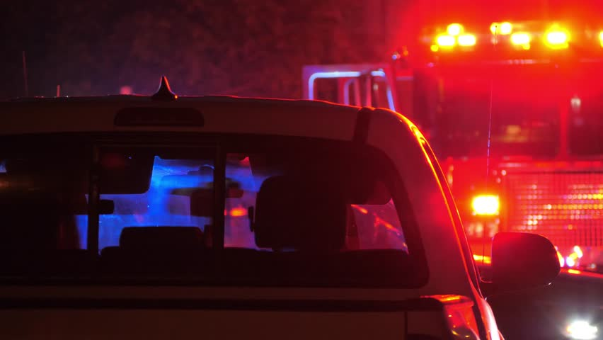 Flashing red  and blue emergency lights  seen through car's interior silhouette at night. Fire truck in background. 4K UHD. | Shutterstock HD Video #1010326259