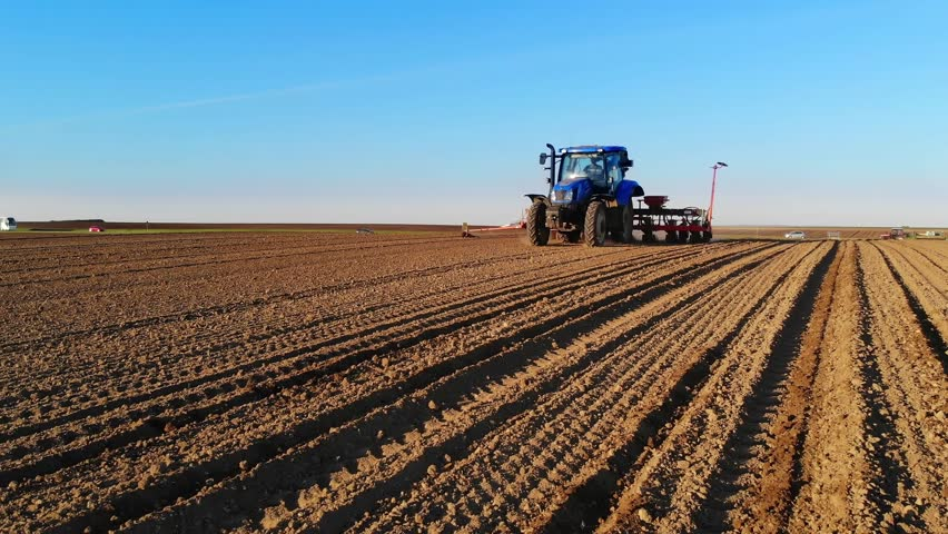 Drone sliding shot of a farmer in tractor seeding, sowing agricultural crops at field at sunset | Shutterstock HD Video #1010354618