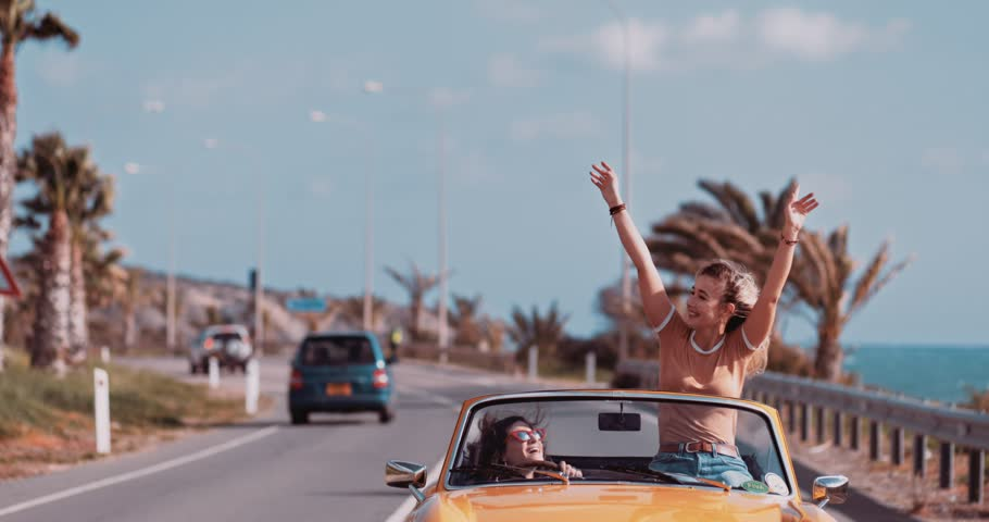 Young women having fun driving convertible vintage car on exotic island palm tree seaside road