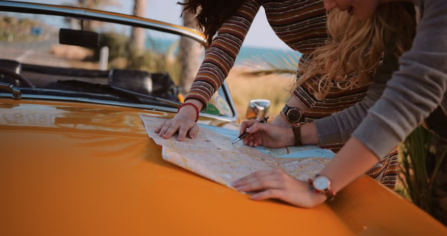 Women on summer holidays road trip with vintage convertible car reading map on palm tree road