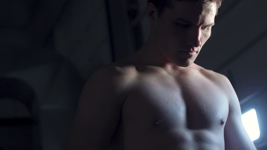 Moody contrast low angle shot tracking around a sexy shirtless  fighter in deep concentration with light reflecting off his body   Shutterstock HD Video #1010372378