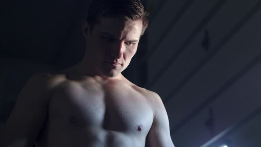 Still low angle shot of a shirtless  fighter in deep concentration in a moody setting with heavy blues and contrast   Shutterstock HD Video #1010374694