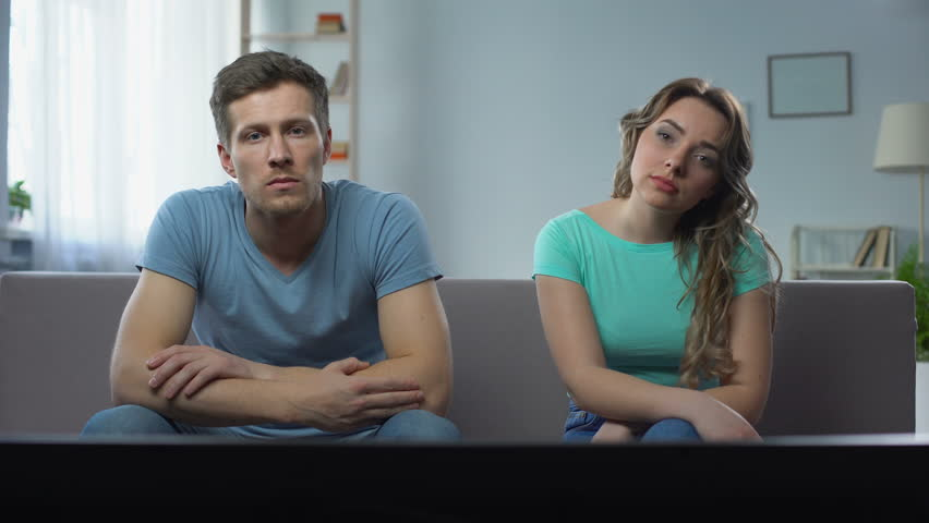 Couple in conflict watching tv silently ignoring each other, relationship crisis