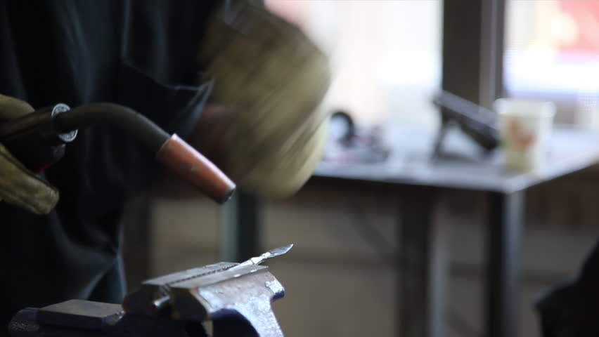 A man wearing a welding helmet and gloves uses an arc welder on a silver metal arrowhead held in a vice, producing showers of sparks which are reflected in the helmet's faceplate. | Shutterstock HD Video #1010384258