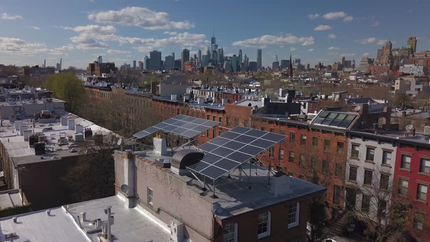 Day flying counter clockwise around solar panels on Brooklyn brownstone