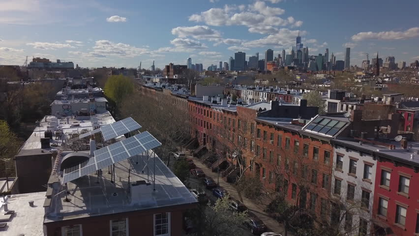 Wider day flying clockwise around solar panels on Brooklyn brownstone