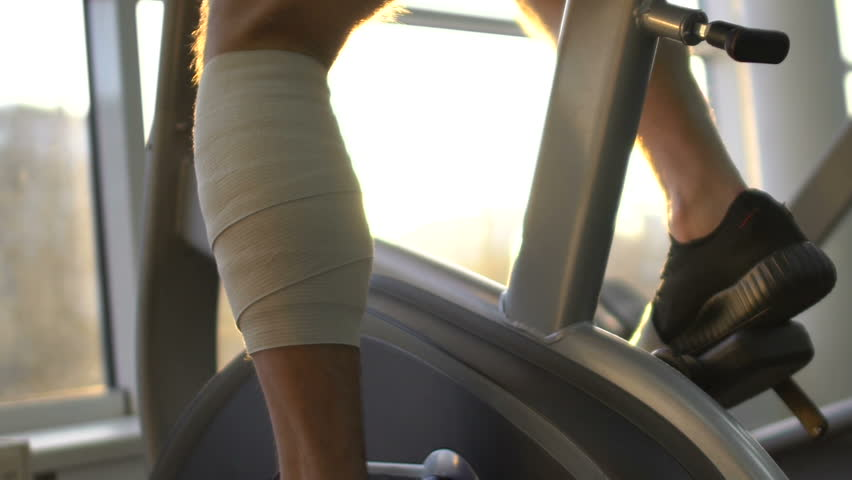 Man with injured leg riding stationary bike in morning sunlight, health recovery