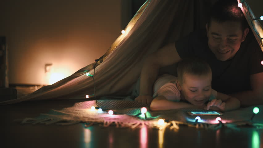 Father and son play and watching smartphone in children's room in tent with Christmas decorations #1010397740
