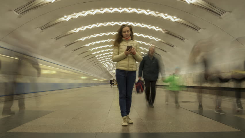 Time Lapse of Woman Standing Still in Underground Metro Station and Using Mobile Phone. Crowd of People and Passing Trains