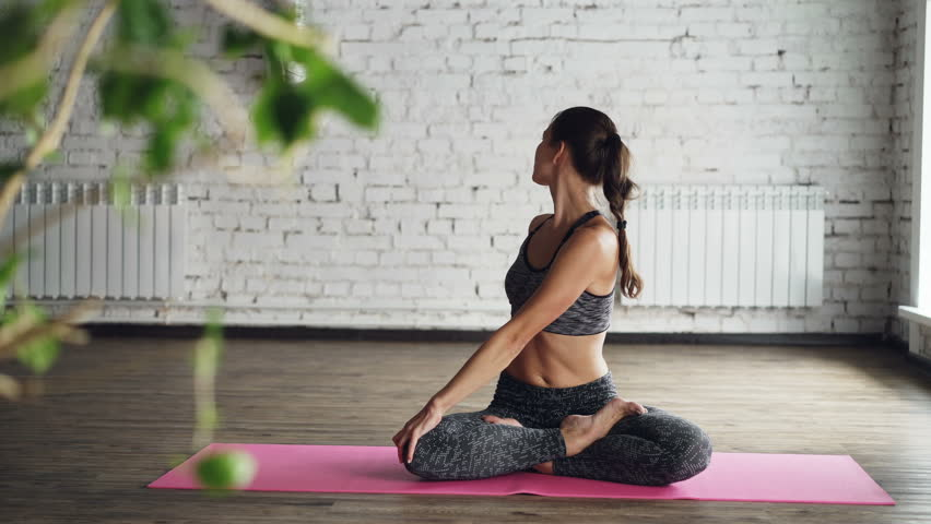 Pretty female yoga instructor is demonstrating body twists in lotus position, stretching and doing namaste then relaxing with hands on knees and breathing. | Shutterstock HD Video #1010404754