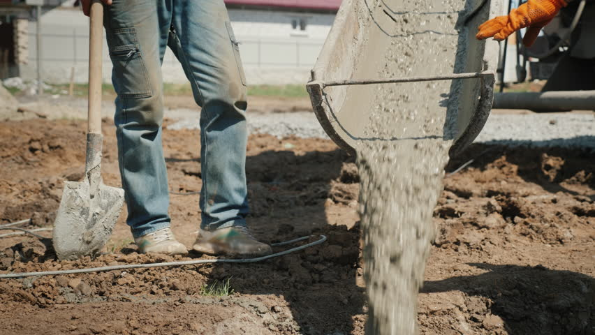 Pouring concrete into the foundation. From the gutter concrete flows, next to the worker with a shovel