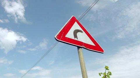panning shot of bending road sign on blue sky background