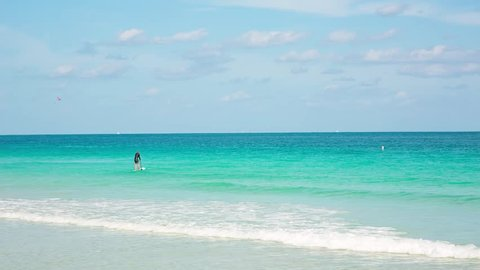 A man with a paddle swims across the ocean on a board at the Miami South Beach