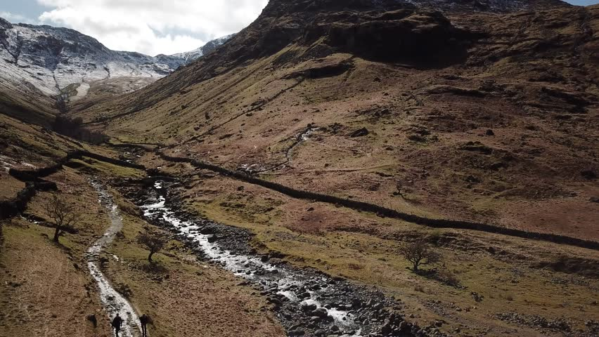 Aerial drone footage of a mountain valley in the Lake District, scrubland below, rocky and snowy peaks with a river running down the center.  Hikers walk along a narrow trail.
