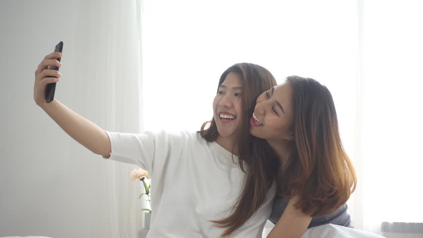 Slow motion - Beautiful young asian women LGBT lesbian happy couple sitting on bed hug and using phone taking selfie together bedroom at home. LGBT lesbian couple together indoors concept. | Shutterstock HD Video #1010425883