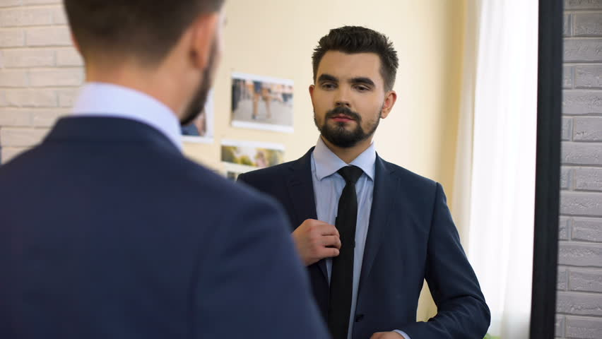 Young man in business suit getting ready for work interview in front of mirror