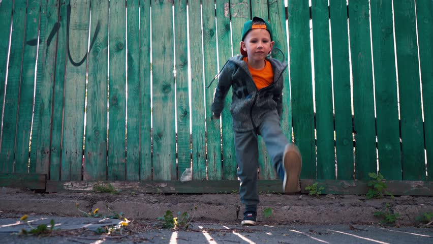 Young breakdancer dances on the background of the old green wooden fence