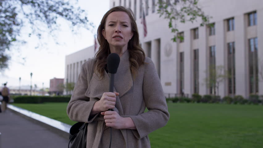 MS smartly dressed female TV journalist talks with microphone in front of old Federal Court building in Downtown Los Angeles. Hand-held, real time 4K UHD. Mute