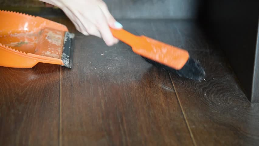 The woman sweeps dust on the floor in the house with an orange brush and broom and brings order and cleanliness | Shutterstock HD Video #1010443574