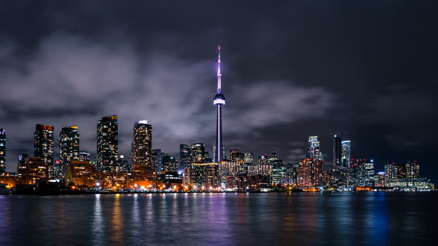 The downtown Toronto Canada city skyline with bright lights and moody storm clouds viewed from the porter island. Fast moving clouds in the sky in a quick paced urban environment.