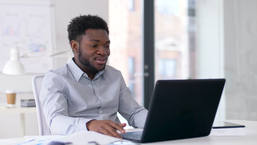 business, technology and communication concept - happy smiling african american businessman having video chat on laptop computer at office #1010447240