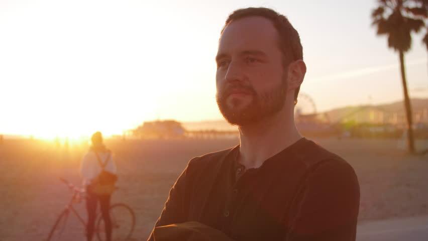 A serious man looks off during sunset at beach | Shutterstock HD Video #1010456300