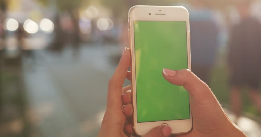 NEW YORK - April 5, 2018:Close up hands woman holding use white phone with green screen on busy street background scrolling pages swiping surfing internet technology smartphone chroma key message