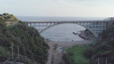 aerial view of an arched road bridge near the ocean