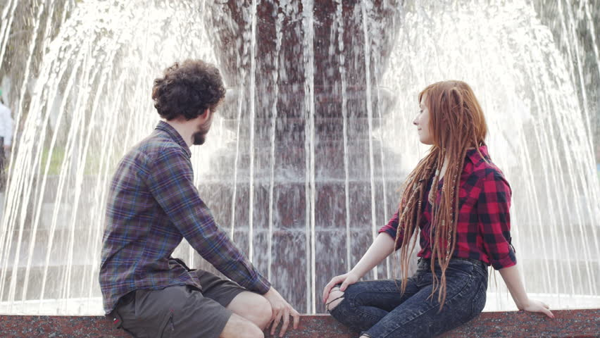 Young couple posing near fountain in sunny summer day, male and female tourists having good time, couple of hipsters on vacation | Shutterstock HD Video #1010471738