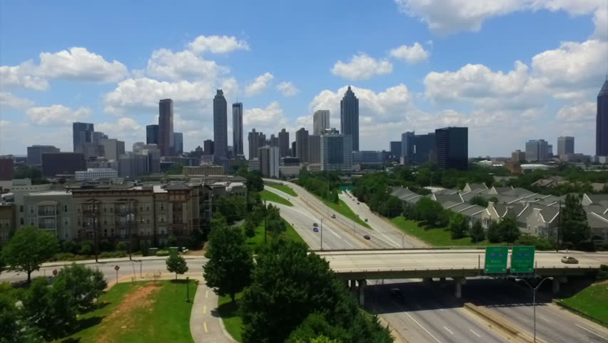 Drone flight over the trees on Freedom Parkway reveals the Atlanta skyline and traffic