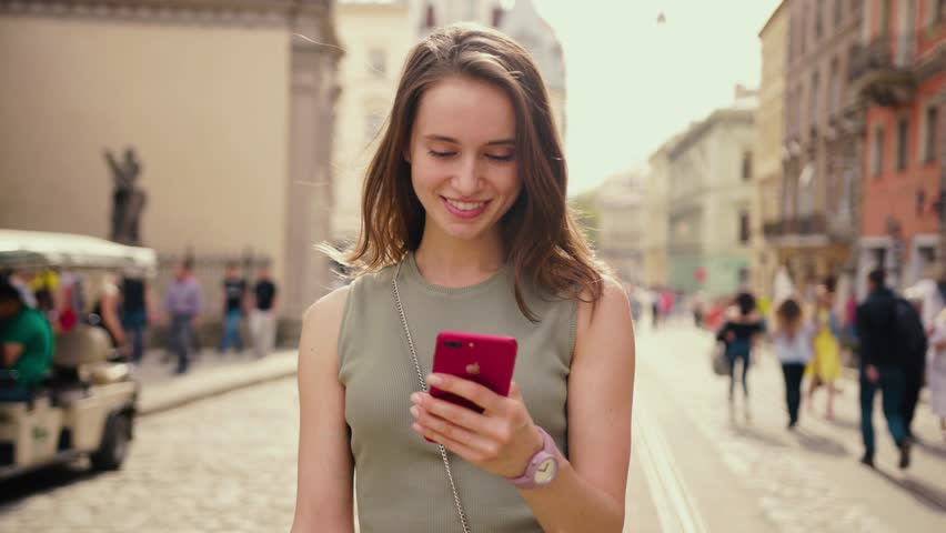 Attractive young woman in a bright sunlight uses phone walk in the city center strokes her hair looks around smile happy summer internet business outside technology eye spring mobile slow motion   Shutterstock HD Video #1010479433