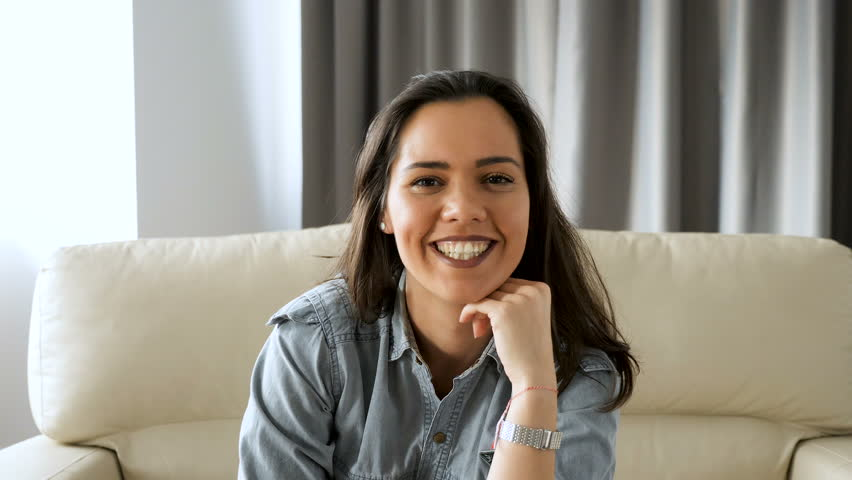 Beautiful woman lying on the sofa is standing to the front of the camera from out of focus to in focus and smiles naturaly. Slow motion footage | Shutterstock HD Video #1010481281