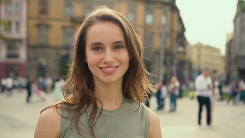 Portrait young attractive smile woman look at camera at city center feel happy fashion girl summer face technology sun beautiful slow motion street