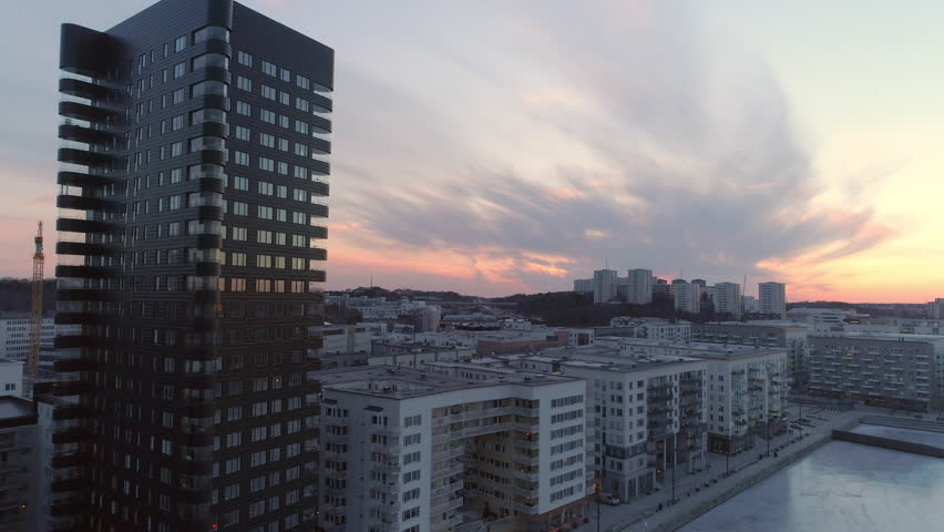 Aerial view of modern office and apartment buildings next to frozen bay in Stockholm, Sweden. Drone shot flying backwards, contemporary residential district at sunset Royalty-Free Stock Footage #1010483765