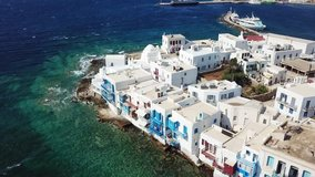 Aerial drone video of iconic little Venice and church of Paraportiani in hora of Mykonos island, Cyclades, Greece