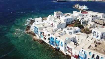 Aerial drone bird's eye view video of iconic little Venice and church of Paraportiani in hora of Mykonos island, Cyclades, Greece