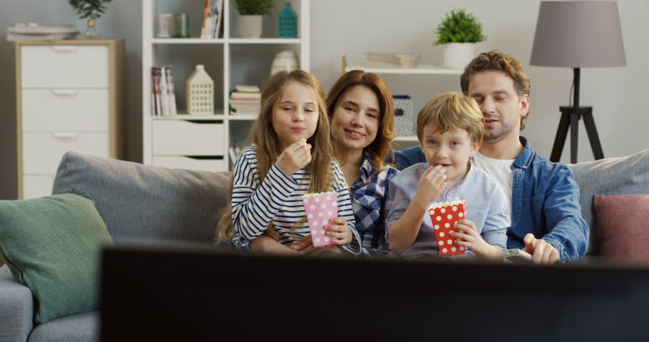 Cheerful caucasian family eating popcorn while sitting on the couch in the living room and watching TV. Portrait shot. Inside