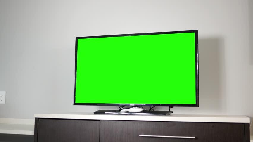 A 4K TV set on top of a modern dresser in ambient room | Shutterstock HD Video #1010493710