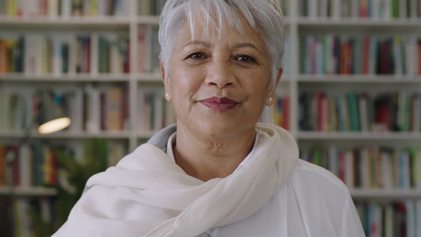 portrait of confident friendly indian middle aged teacher standing in library close up Royalty-Free Stock Footage #1010501450