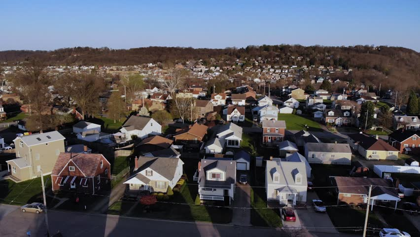 A dusk early Spring slow forward aerial establishing shot of a typical residential neighborhood in a Western Pennsylvania small town. Pittsburgh suburbs.