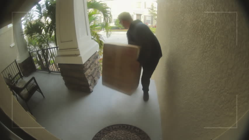 Person stealing delivery package from porch steps, surveillance camera view
