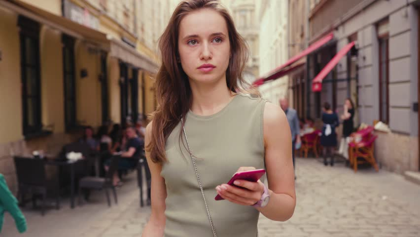 Serious young woman in a bright sunlight uses red phone while walk in the city center summer internet business outside technology eye spring mobile slow motion street attractive close up portrait | Shutterstock HD Video #1010521124