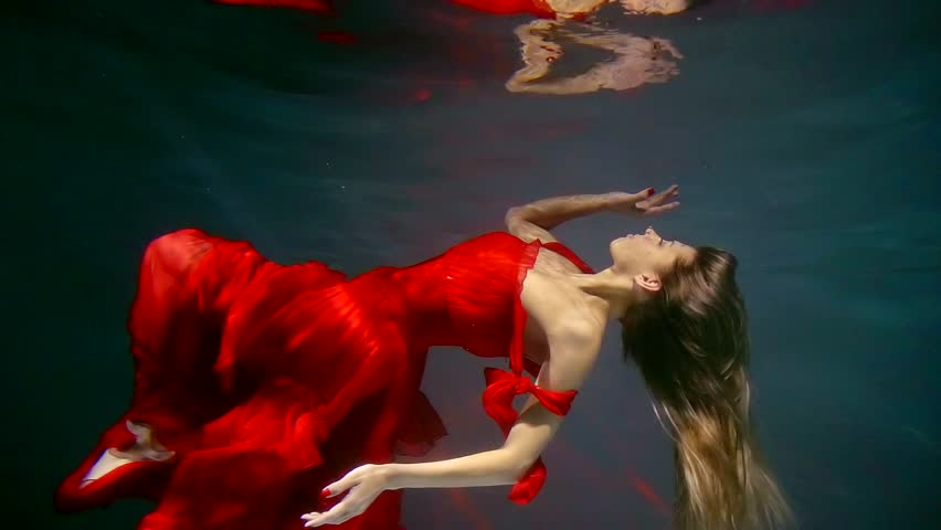 Attractive blonde woman floating underwater wearing beautiful red dress.