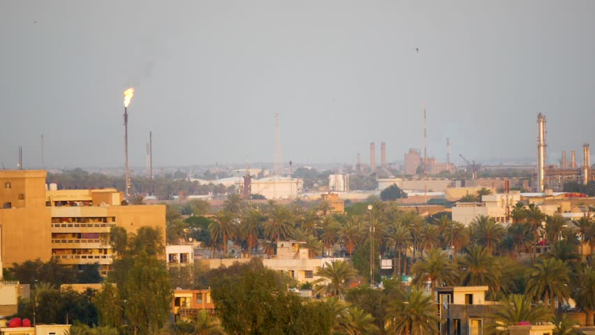 Baghdad, NA / Iraq - 04 15 2018: Baghdad, Iraq April 2018: Panorama of the Baghdad skyline and oil field at sunset