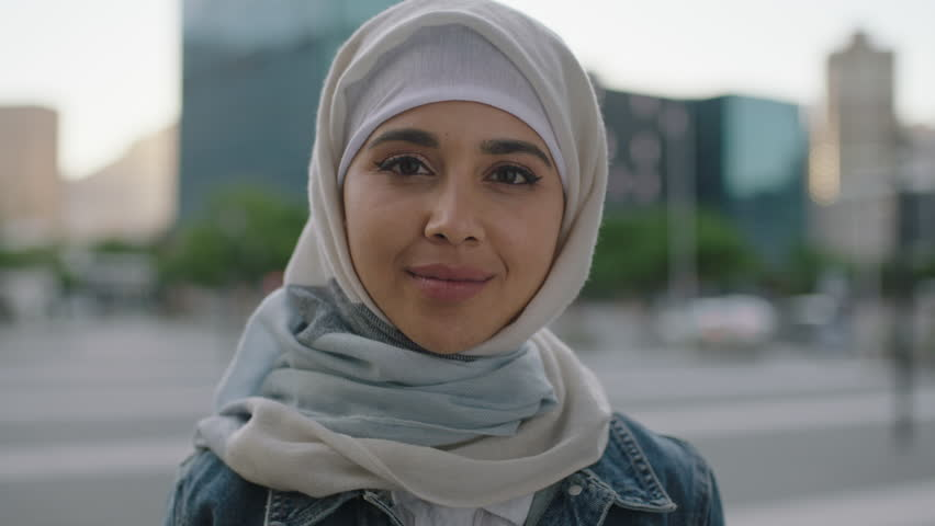Portrait of young independent muslim woman looking at camera smiling cheerful wearing hijab headscarf in urban city at sunset