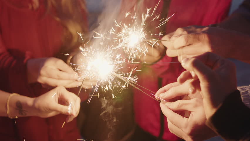 Group of friends celebrating holding sparklers on beach enjoying new years eve beach party at sunset real people series Royalty-Free Stock Footage #1010551091