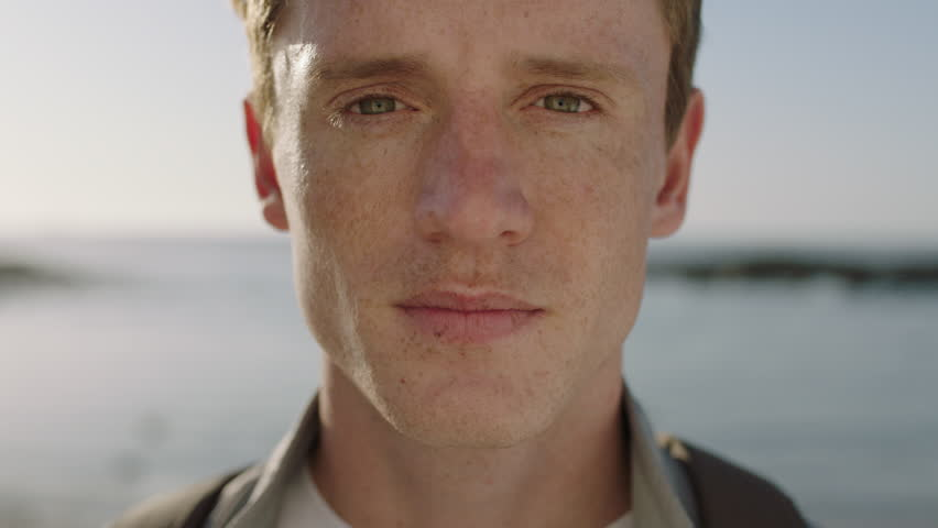 Close up portrait of handsome young man looking thoughtful pensive on seaside background focused confident #1010551097